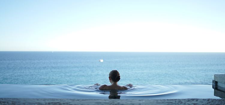 Lady in a mineral bath at a day spa overlooking the ocean.